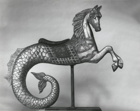 Black and white photo of carousel figure, a horse with saddle and fish-like tail