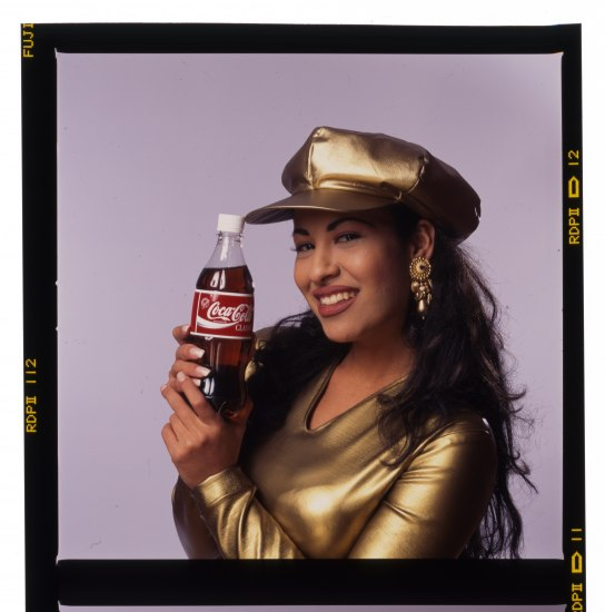 Selena in gold lamé top with matching hat, holding a Coca-Cola