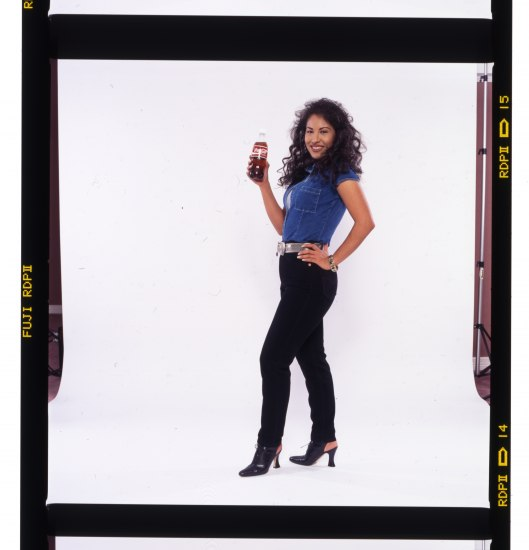 Selena in black denim pants and blue shirt, holding a bottle of Coca-Cola.