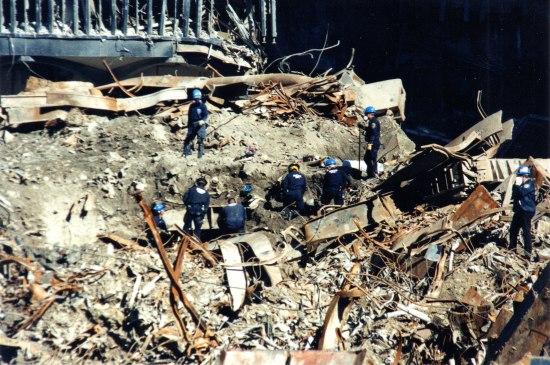 Photo of the destruction after September 11, 2001, in New York City. Workers in blue helmets and uniforms scramble around a pile of destruction, bent metal, and ruins.