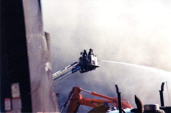 Photo of World Trade Center site after attacks of September 11, 2001. Two or three workers in hard hats and uniforms are in the cherrypicker of a crane, shooting a fire hose downward in a gentle arch. A battered wall or part of a building visible left.