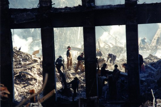 Photo of workers at September 11, 2001, destruction pile seen through columns of partially destroyed building. They wear hardhats and uniforms. Smoke rises here and there.