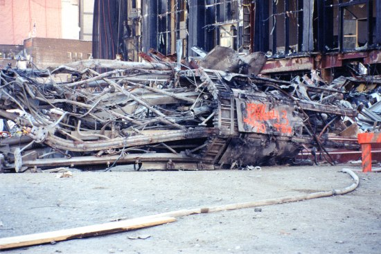 Photo of destruction in New York City after September 11, 2001. Collapsed industrial-looking part of a building with many pipes, columns, and wires. In background, broken windows. Ash and gray.