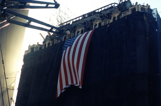 Photo of a building still standing after attacks of September 11, 2001. A big American flag hangs from a building. The building is draped in black.