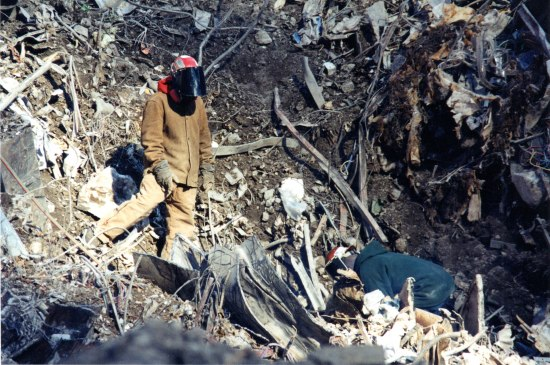 Worker in helmet and face shield and drab brown/yellow uniform. Pile of debris.