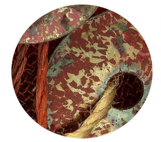 A photo cropped to the shape of a circle. It shows and extreme close-up of sequin from the Ruby Slippers, including a thread.
