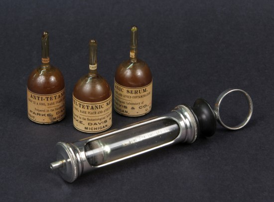 "Medical items. Three small bottles labeled ""anti-tetanic"" and what appears to be part of an injection device."