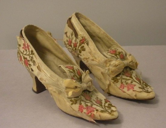 A pair of cream colored shoes with flower embroidery, short heels and bows