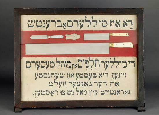 Black, white, and red shop sign with Yiddish text