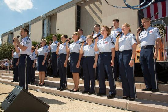 People in uniform singing outside the museum