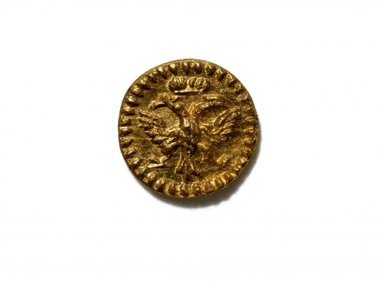 Image of gold metal coin with a tree or bird design.