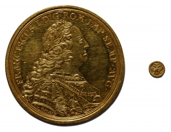 Image of two coins. One is huge, one is small. Huge one includes portrait of a man in profile with long curly hair and rich attire. Small one includes image of tree.