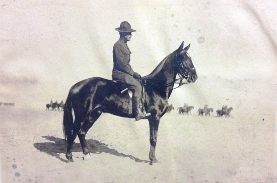 Soldier in uniform on a horse. Black and white photo. In distance, a few more soldiers on horses. Desert sand.