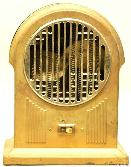 Gold-colored space heater with switch, circle-shaped grate, and sloped top.