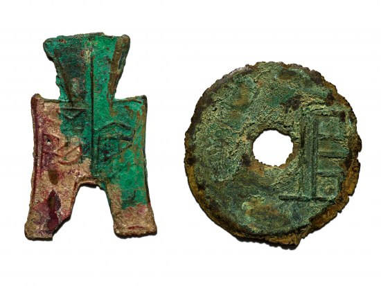 Photograph of two pieces of money. On left, a rectangular-shaped metal with handle-like protrusion and notch. On right, a coin-shaped metal object with hole in center.
