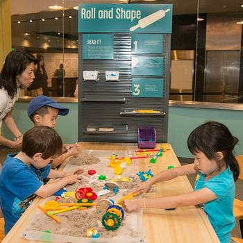 Kids and an adult playing at a station in Spark Lab