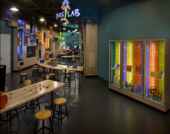 Photograph of museum space with large Spark!Lab sign overheard. Desks, stools, and supplies for a hands-on activity can be seen among display cases and colorful setting.