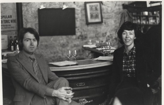 Black and white photo of a man and woman sitting at a U-shaped bar with place settings that include two wine glasses and sheets of paper (wine tasting sheets, perhaps).