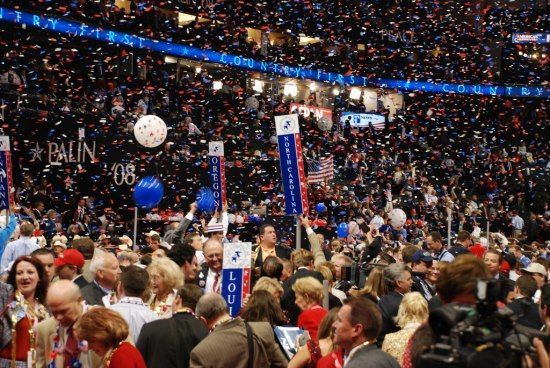 a view of the delegation floor of the 2012 Republican convention. There is a crowd of people, confetti and balloons. State standards which are basically state name signs on poles are visible throughout the floor