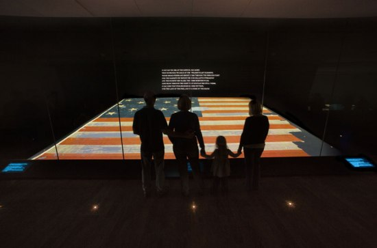 A family in silhouette stands in front of a large flag displayed horizontally