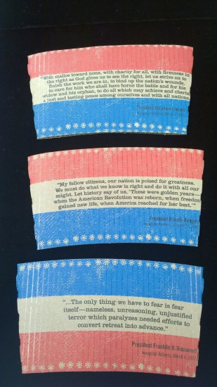 Three disposable coffee sleeves. They have red, white and blue stripes and each has text from the inauguration speech of a different president
