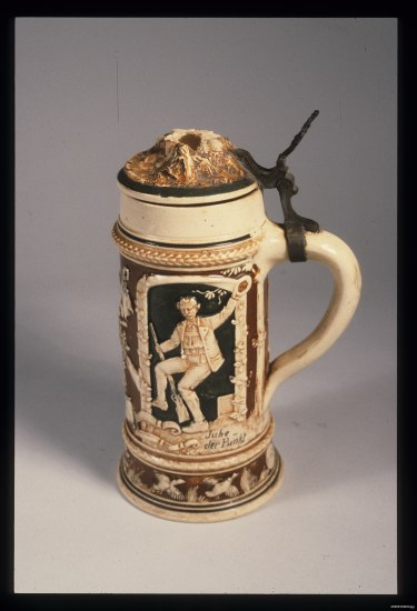 A large mug with a lid and handle. It is made from a light colored substance but has carvings with dark backgrounds, including one of a man