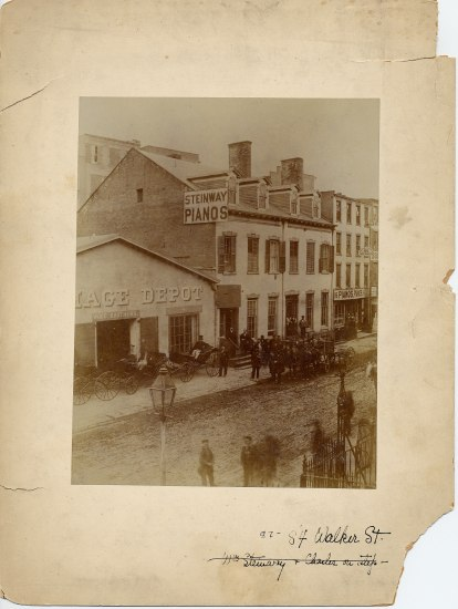 """A photograph of a building labeled """"Steinway Pianos"""" on an unpaved street. The photograph is yellowed with age, with folds and rips in the cardboard border."""
