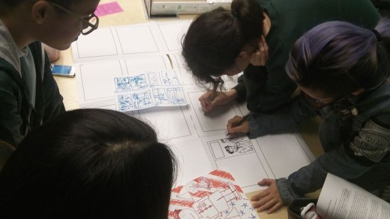 Four students lean over white sheets of paper. Two of them draw comics into boxes with markers.
