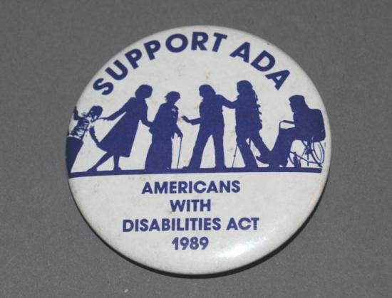 "White pin with purple graphic and text. ""Support ADA / Americans with Disabilities Act 1989."" Graphic, stylized images of six people, young and old."
