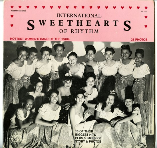 Album cover with pink band across the top and black text. Black and white photo of smiling women in long skirts.