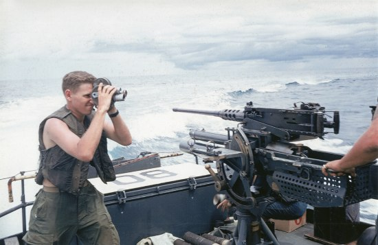 On a boat with waves in the background, a young man with blonde hair holds a video camera to his face. He wears a military vest and pants with bare arms. In front of him--the subject he is filming--is a gun or other military equipment on the boat. An operator's forearm is visible holding/manipulating the gun or equipment.
