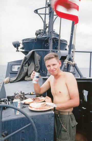Young man with no shirt on military boat on a river or ocean. He holds a pop can. Two plates of food in front of him.