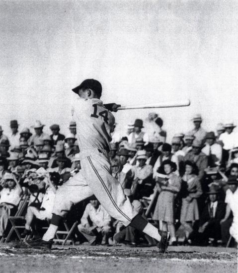 Baseball player after swinging for the ball, about to run, crowd watching