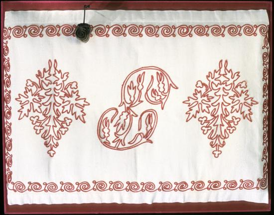 White fabric with flourish-y designs in red thread