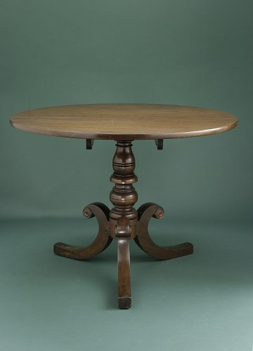 A wooden table on a green background. The table is flat and simple on the top, with an ornate leg in the center. Three curves of wood support the middle structure.