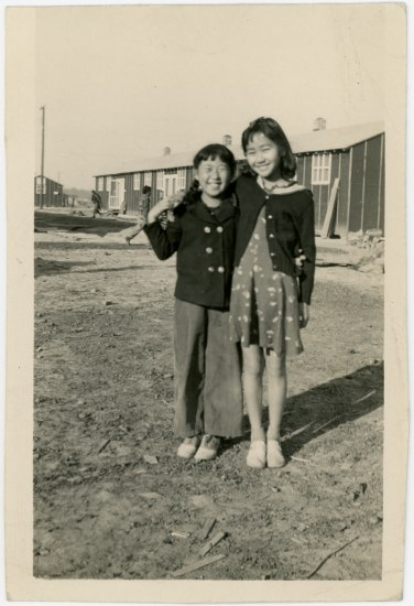 Black and white photo of two smiling children. Standing outside, with a very plain building behind them. They are both smiling.