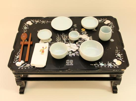 Photo of tea service on black tray with floral designs in corners
