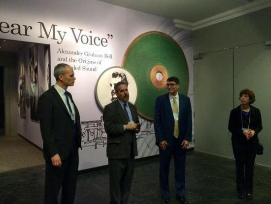 Three men and one woman stand in front of an exhibit wall