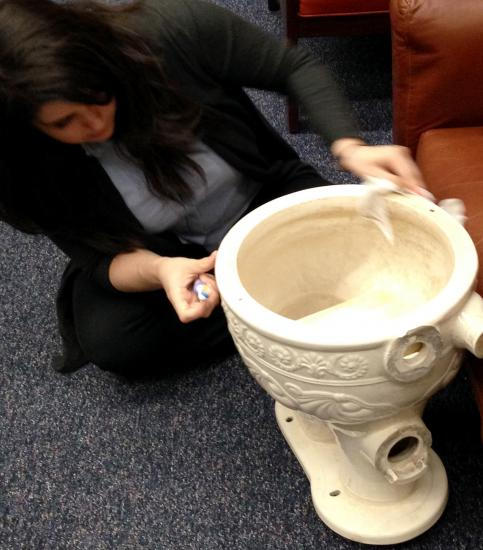 Staff member cleaning historic toilet with toothbrush