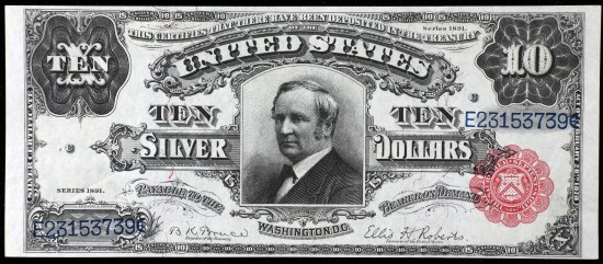 A piece of currency with black print over a white background, with a red, petal-like decoration in the righthand corner. There is a somber man printed in the middle and decorative flourishes around the edges and surrounding text in the center of the bill.