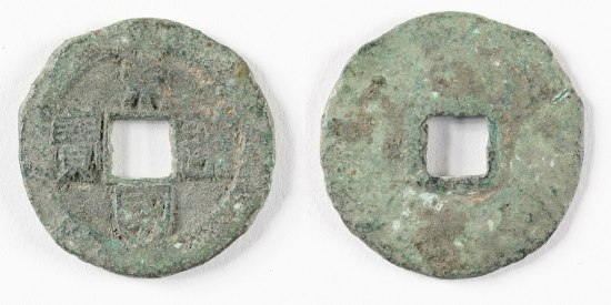 A round coin with a square removed from the center and aged markings