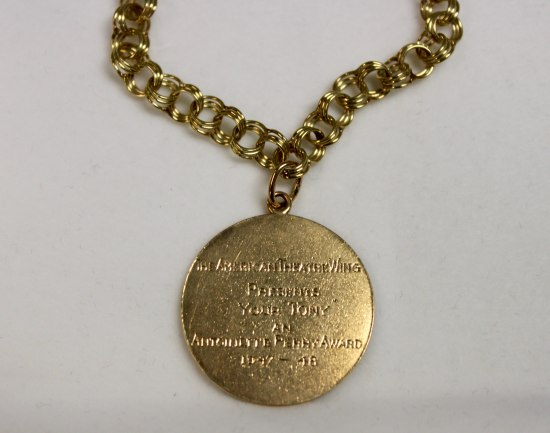 Close-up of a gold charm bracelet. The back of the pendant/charm is visible and has words etched into it.