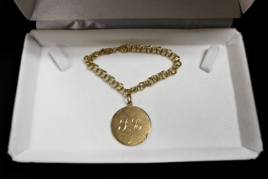 "A golden bracelet sitting in a jewelry box. The bracelet has a round pendant/charm attached to it with letters ""J L"" inscribed in cursive script."