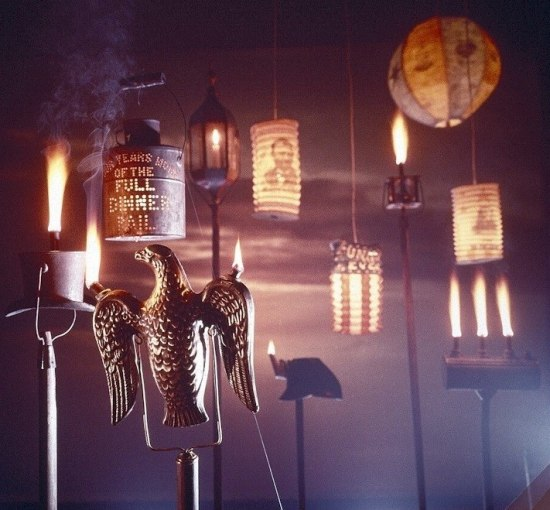 Color photo of illuminated torches, about eight of them. Variety of shapes: eagles, top hat, lantern, dinner pail.
