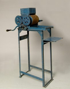 Photo of blue-painted machine with tall legs. Crank and press plus feeder chute.