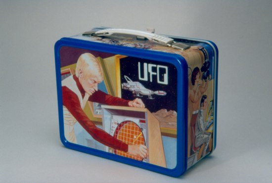 A lunchbox with a white handle, blue borders, and illustrations of people on a space ship.