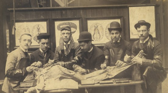 A lack and white photograph of a group of young men standing behind a table on which is a human body which has been dissected