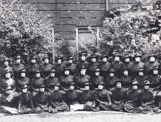 Black and white group photo of women wearing uniform coats and hats.