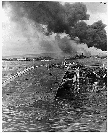 The view of the photograph appears to be over a bay, where a large boat is on its side in the water and looks to be sinking. There is black smoke in the background and other ships. You can see buildings by the water.