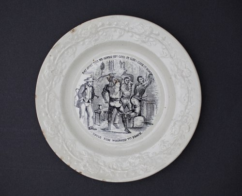 "A white, round porcelain plate with an illustration of a black man being whipped by two other black men.On the left of the illustration, a white man in a suit watches. The text above the image says, ""Pay away till he gives up! Give it him! Give it him!"" Below, the text reads, ""Uncle Tom Whipped to Death."""